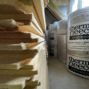 The left hand side shows a pile of flat layers of insulation. To the right hand side, the insulation is wrapped in round plastic bundles labelled 'thermal fleece'. Communion Architects, Hereford, Herefordshire.