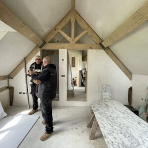 Pitched roof attic room with two men dress in black surveying the work done. Timber beams and Alex supports are visible. Plaster boards scatter the floor for use in another room. Communion architects, Hereford, Herefordshire.