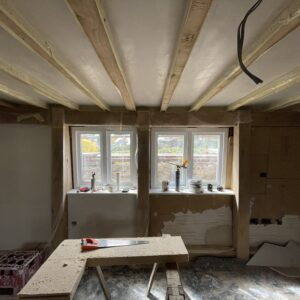 Inside a room under construction. Looking at a small timber framed window with exposed timber beams above and walls part painted, part plaster, with tools and timber on the floor in front. Part of an effort to conserve a fire damaged cottage, Communion Architects, Hereford, Herefordshire.