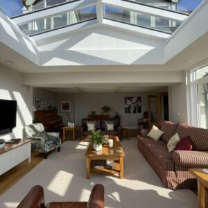 Orangery extension interior - an apex roof light floods the new sitting room extension with sun rays, Communion architects Hereford