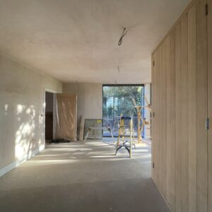 Looking through an oblong room, freshly plastered walls, timber cupboard doors to one side and full height glazed windows at the far end. Communion Architects, Hereford.