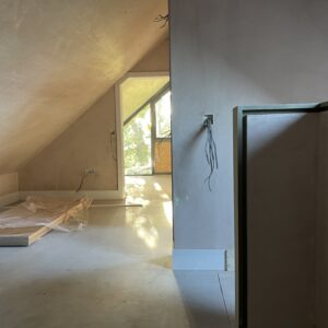 inside an attic room with sloping roof and freshly plaster walls. The end wall is glazed with golden autumnal sun shine through. New House designed by communion architects Hereford