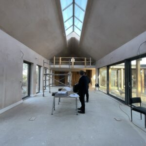 freshly plastered main room interior for a new build in Herefordshire. glazed walls and an apex roof with a full length sky light. communion architects Hereford.