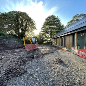 A small yellow digger clearing a muddy area while in the right hand side of the image is a new single storey house with a slate roof and glass and timber walls. Communion Architects Hereford.
