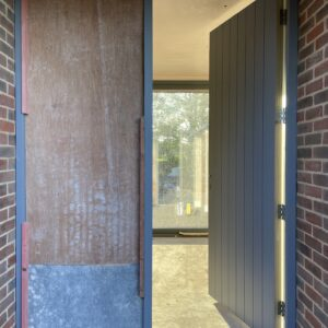 Large grey front door ajar, new house, communion architects