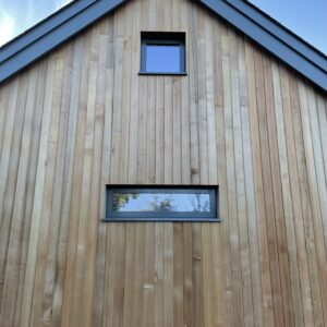 End wall of a new house, a pet slate roof, facade is boarded with fresh cedar. Communion Architects Hereford