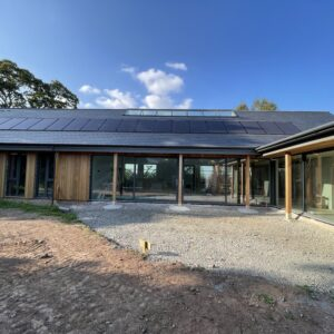 a L shaped house, single storey with a slate roof, full height glazing for the walls and timber columns supporting overhanging eaves. Communion Architects, Hereford.