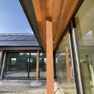 L-shaped house - close up of timber columns and timber eaves supporting an overhanging roof, protecting a wall of glass, communion architects Hereford.