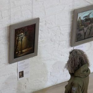 A visitor to the Risen! exhibition at St Peter's, Peterchurch looking at one of Mark Cazalet's London Stations of the Cross
