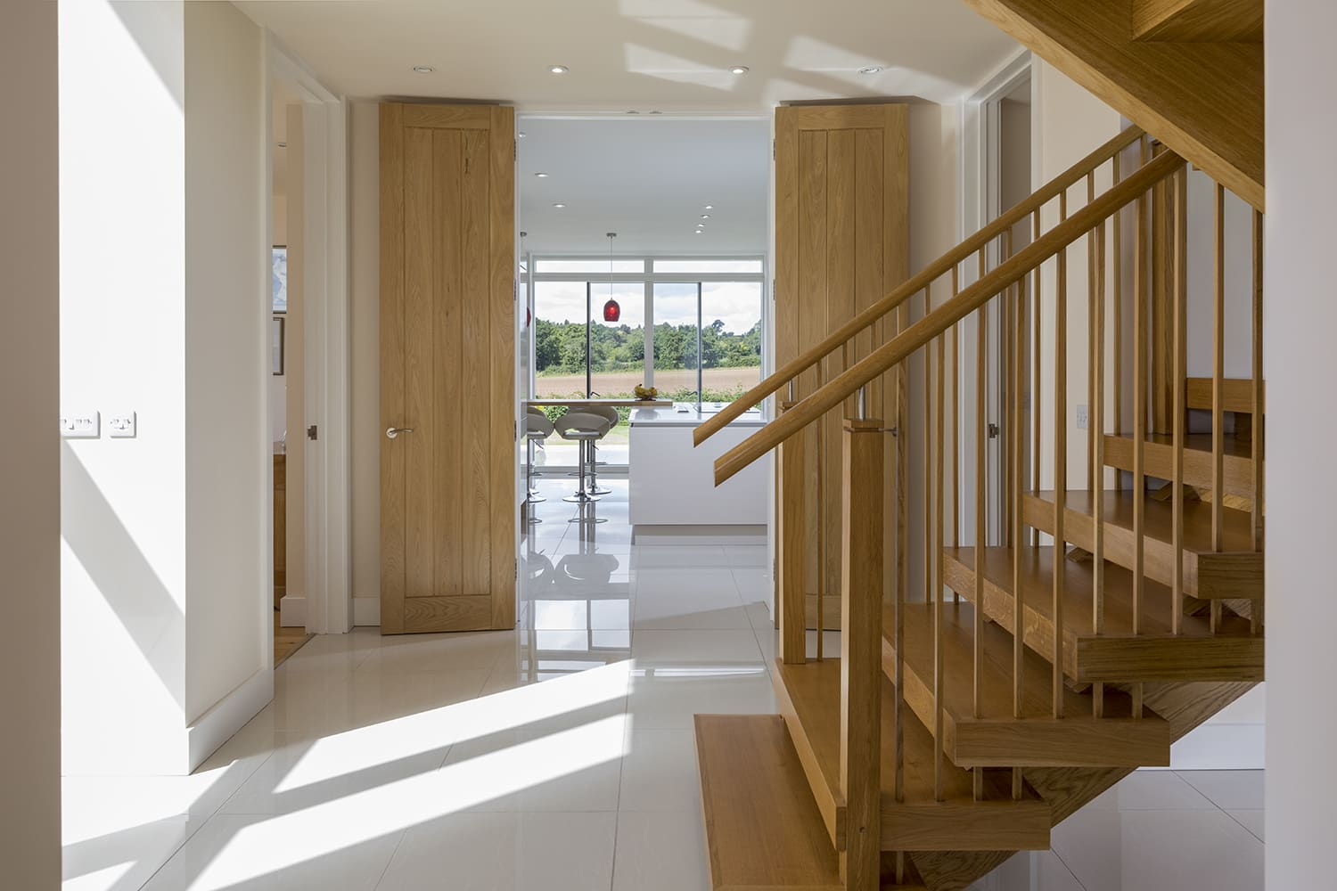 Bespoke wooden staircase rising from tiled hallway