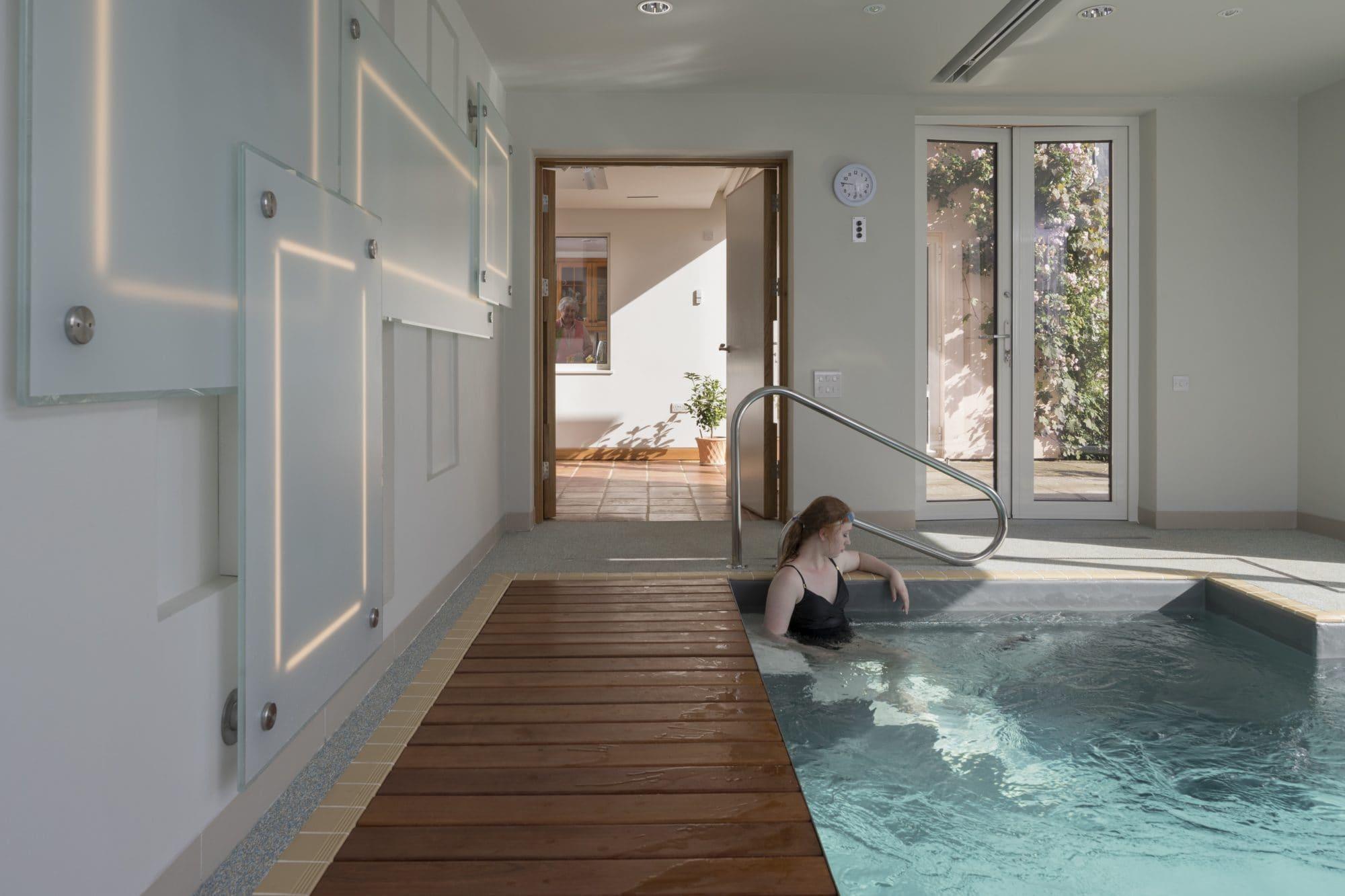 Wooden walkway alongside indoor swimming pool